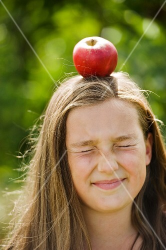 A girl with an apple on her head