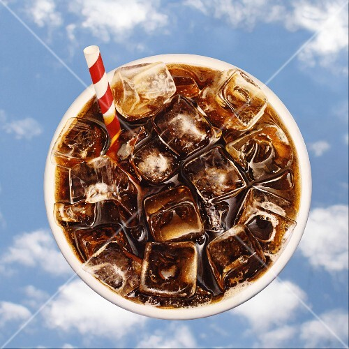 A bird's eye view of a glass of cola and a straw against a blue sky background (illustration)