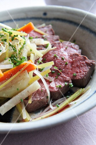 Beef, root vegetables, chives, salt and pepper in a soup dish