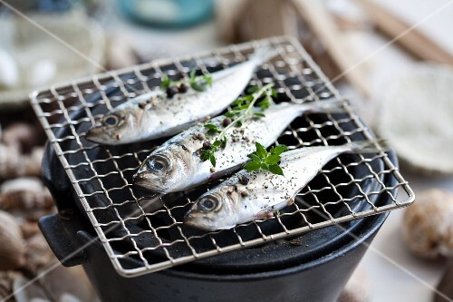 Fish on the barbecue, with sesame seeds, peppercorns and thyme