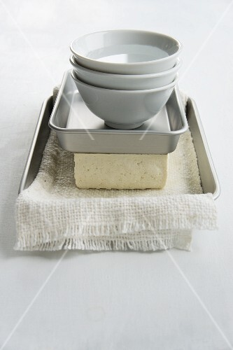 Tofu being drained (weighed down with dishes full of water)