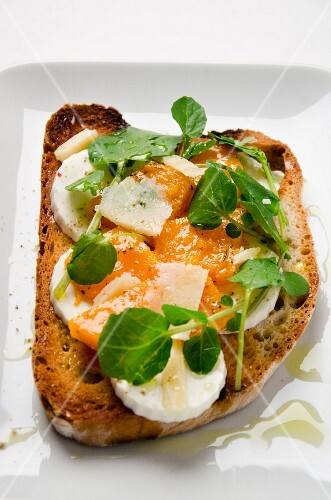 A slice of toast topped with cheese, pumpkin chutney and bittercress