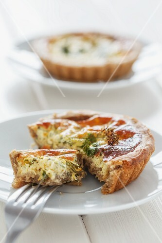 A mini quiche with herbs with a bite taken out