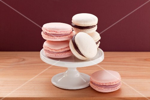 A small cake stand with pink macaroons and white macaroons with chocolate filling