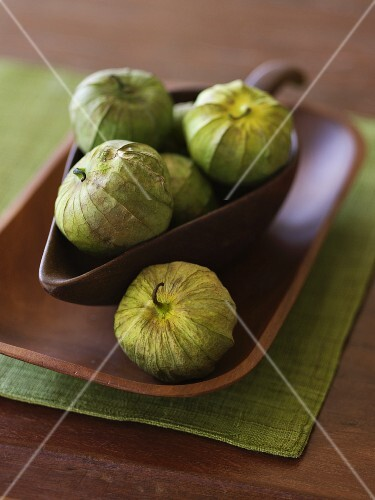 Fresh Tomatillos in a Wooden Bowl and On a Wooden Tray
