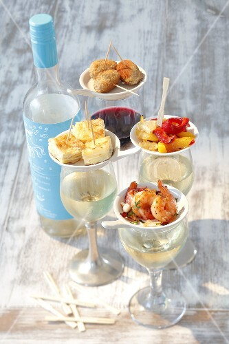 Various tapas on wine glasses