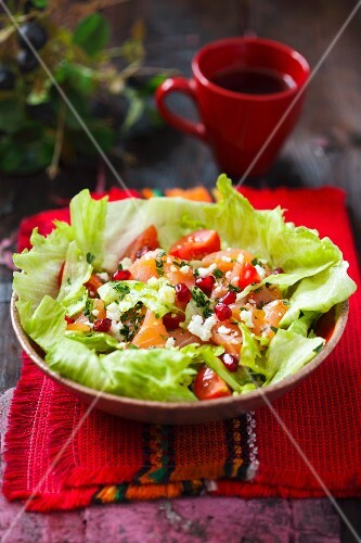 Salmon salad with tomatoes, feta cheese and pomegranate seeds on iceberg lettuce
