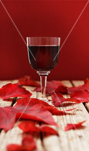 A glass of red wine surrounded by red autumnal leaves