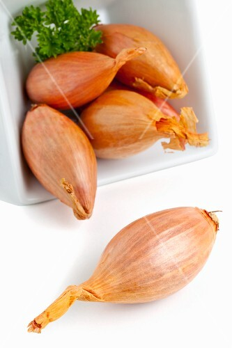 Whole shallots in a white dish