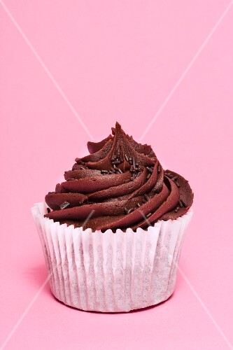 A chocolate cupcake on a pink surface