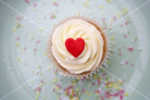 A cupcake decorated with light frosting and a red marzipan heart