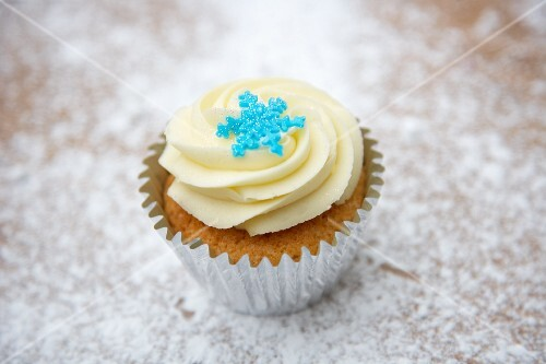 A cupcake decorated with light frosting and a sugar snowflake