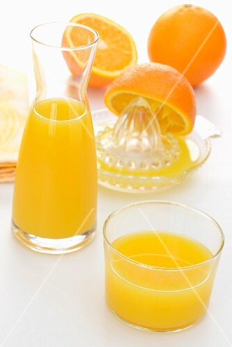 Freshly squeezed orange juice in a glass and a glass carafe