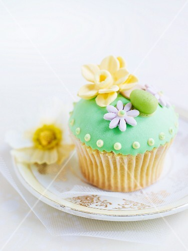 A cupcake decorated with green frosting and marzipan decorations