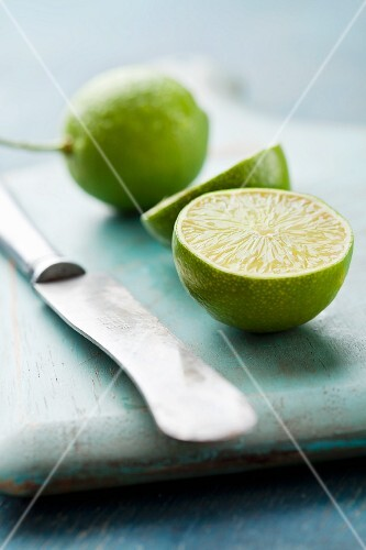 A halved lime and a knife on a blue wooden board