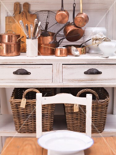 Shiny copper pots on a country house-style kitchen buffet with two large wicker baskets underneath