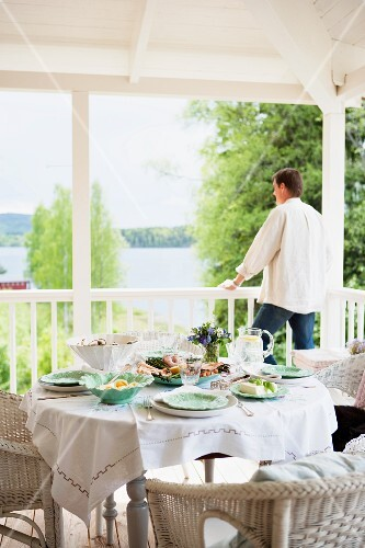 Set table on veranda with view of lake