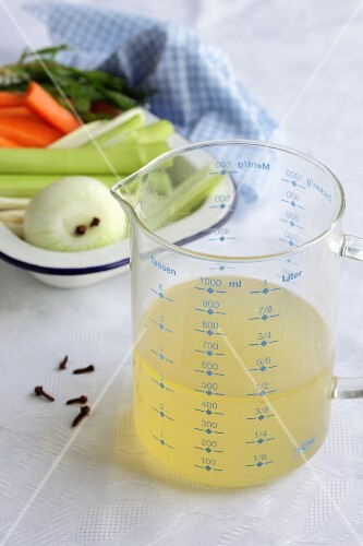 Chicken broth in a measuring jug, soup vegetables and cloves