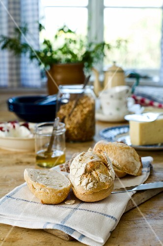 Fresh breakfast rolls on rustic dining table