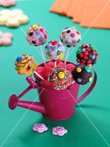 Cake pops decorated with colourful chocolate beans in a watering can