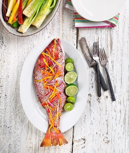 Whole Cooked Snapper Garnished with Shaved Vegetables and Limes; From Above