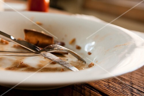 A Dirty Plate with Leftovers and a Fork and Knife