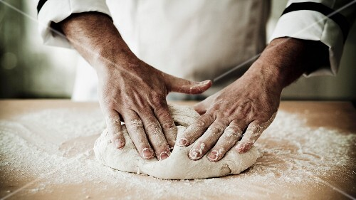 A chef kneading pizza dough