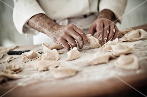 A chef rolling fresh tortellini in flour