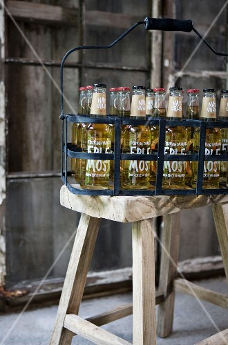Full bottles in black metal, vintage bottle carrier on rustic wooden stool
