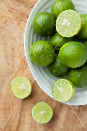 Fresh limes, whole and halved, in a dish
