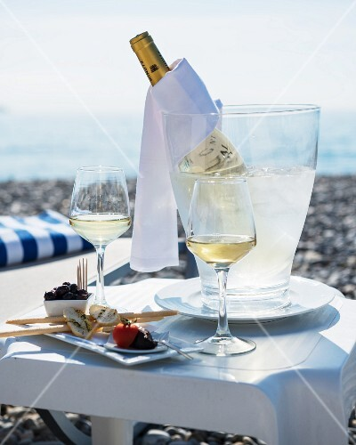 A table laid for two at the beach, with appetisers, glasses of white wine and a bottle of wine in a chiller