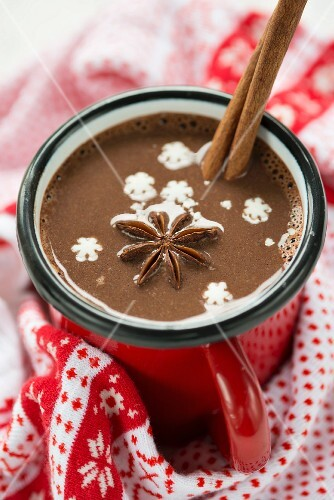 A cup of hot chocolate with star anise, a cinnamon stick and snow flakes