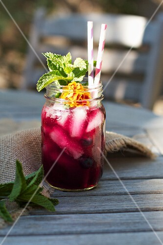 Blueberry Mint Tea with Edible Flowers, Mint Leaves and Straws in a Mason Jar
