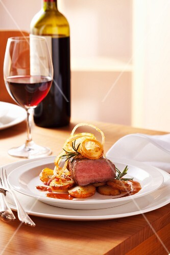 Sirloin of beef with sauté potatoes, onion rings and rosemary