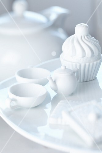 A mini teaset and cupcake made of porcelain