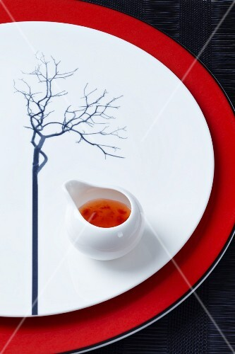 A plate decorated with a tree and with a pot of Asian sauce