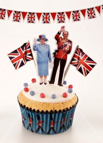 A cupcake topped with Queen Elizabeth II of England and the Duke of Edinburgh