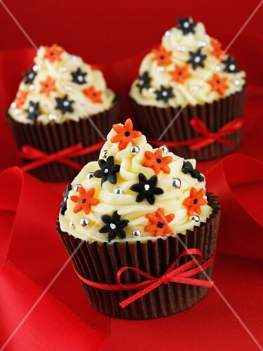 Cupcakes decorated with buttercream, sugar flowers and a red ribbon