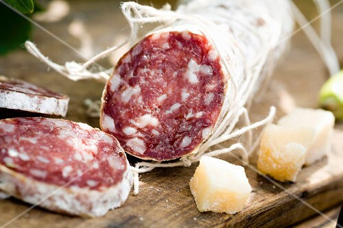 A salami, partly sliced, and cubes of parmesan