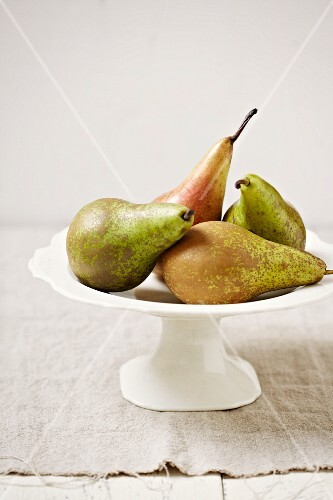 Four pears on a cake stand