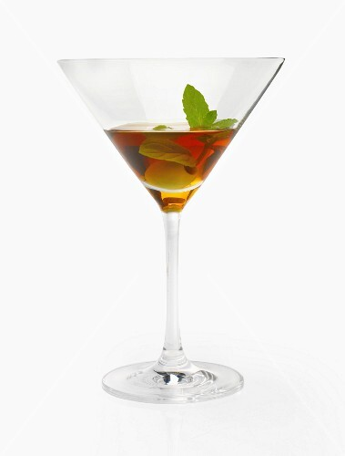An alcoholic drink with olives and mint