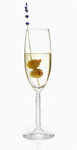 A glass of prosecco with two olives