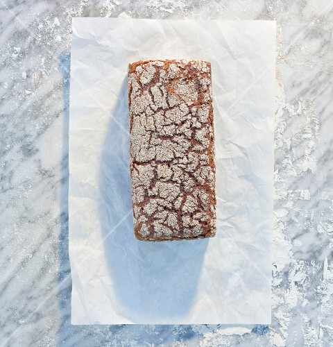 A wholemeal sandwich loaf on paper, on a marble slab, dusted with flour