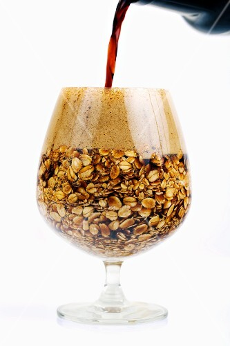 Oatmeal Stout Beer Being Poured into a Snifter Filled with Oats; White background