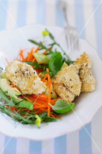 Fillet of fish with a sesame seed crust on a carrot and avocado salad