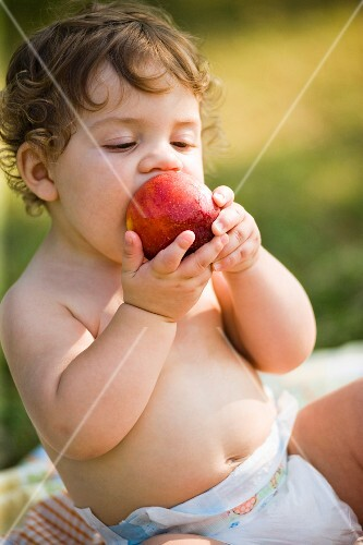 A small child biting appreciatively into a peach