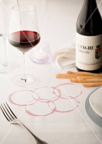 The Olympic rings marked in red wine on a white tablecloth