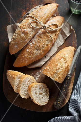 Small baguette rolls, whole and sliced, on a wooden board