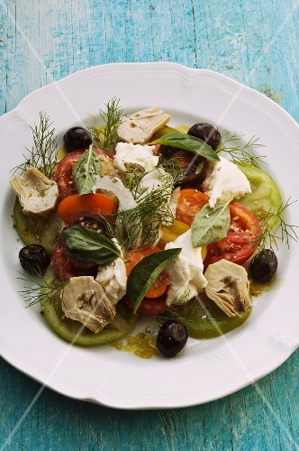 Tomato salad with mozzarella, artichokes, olives and herbs