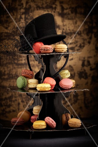 Macaroons on a tiered cake stand with a hat